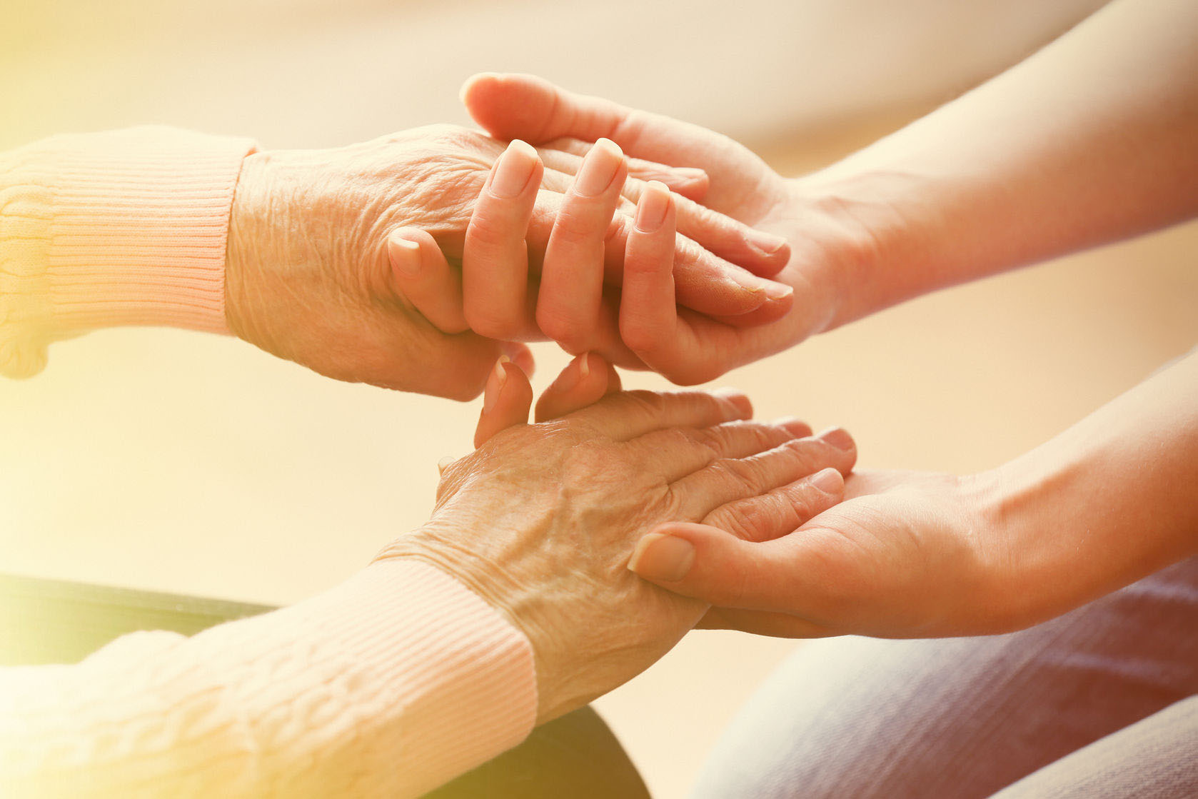 36591099 Old And Young Holding Hands On Light Background, Closeup